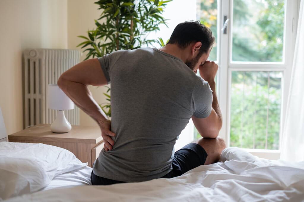 Man feeling backache after sleeping in bed